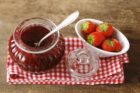 High angle view of a rustic still life with fresh strawberries and strawberry jam in a pretty glass jar arranged on a cheerful red and white checked cloth on an old wooden tabletop photo