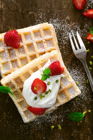 Delicious waffle topped with whipped cream and ripe red fresh strawberries sprinkled with sugar and served on a rustic wooden surface photo