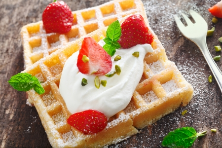 Closeup of a dollop of fresh whipped cream and sliced fresh strawberries topping a crisp golden waffle photo
