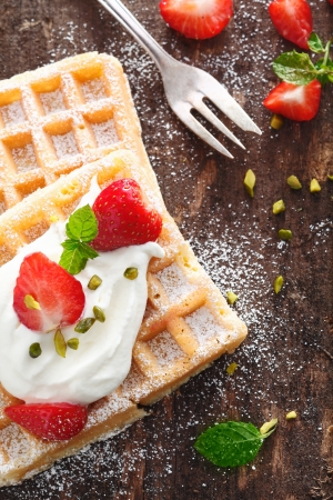 Crisp golden waffle topped with strawberries and whipped cream and garnished with mint on a rough wooden table top photo
