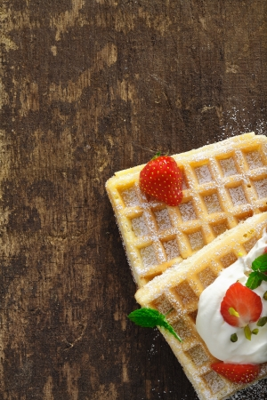 Overhead view of golden waffles with cream and strawberries on a rough textured wooden table with copyspace photo