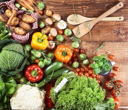 Overhead view of an array of different fresh country herbs and vegetables on a wooden kitchen surface ready to be used as ingredients in vegetarian cuisine Stock Photo - 17853048