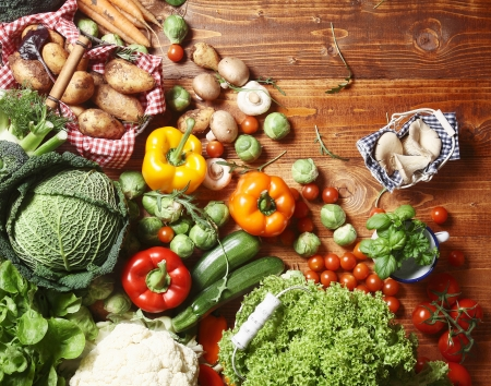Overhead view of a delicious assortment of farm fresh vegetables, herbs and mushrooms spread out on a rustic wooden table Stock Photo - 17853032