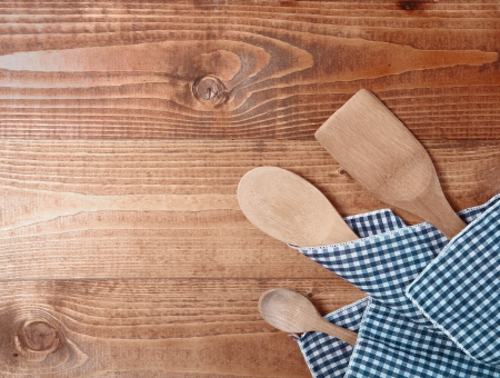 Three wooden spoons wrappen in a cloth on wooden surface photo