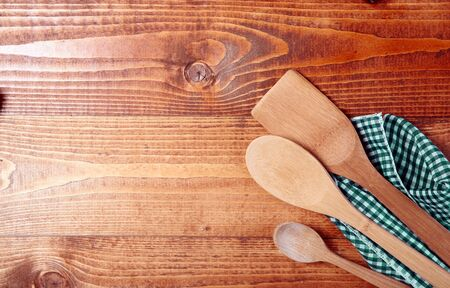Three wooden spoons wrappen in a cloth on wooden surface Stock Photo - 17853029