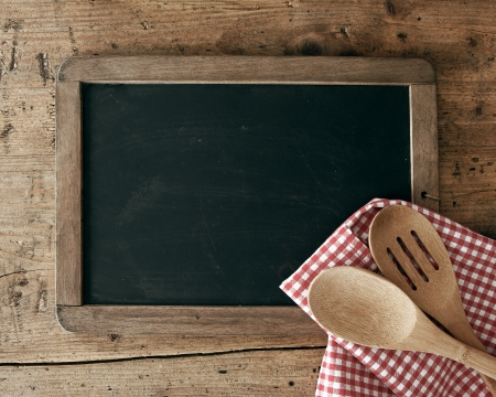 menue: Blackboard on wooden surface and serving spoons