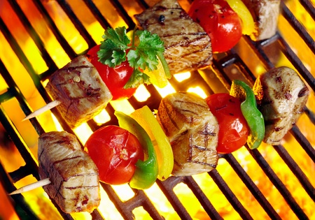 Closeup of two delicious meat kebabs skewered with peppers and tomato sizzling over the coals of a barbecue photo