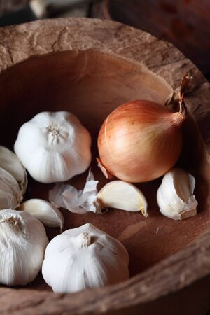 flavouring: Fresh garlic cloves and brown onion in an old rustic wooden bowl for use as pungent flavouring in cooking
