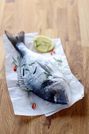 enjoyable: Whole raw fish on crumpled paper lying on a wooden kitchen table waiting to be filleted to cook as an enjoyable seafood dinner Stock Photo
