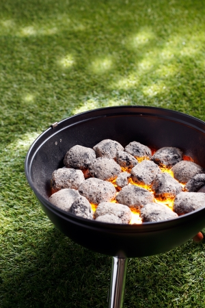 coals: High angle view of glowing hot charcoal coals in a small portable barbecue standing on grass in preparation for cooking a healthy outdoor meal