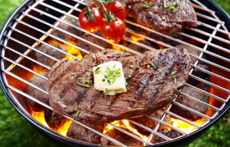 High angle view of a portion of lean steak topped with butter and herbs grilling over a glowing fire in a portable barbecue outdoors on grass photo