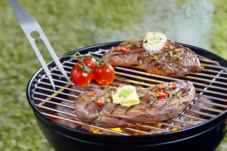 cookout: Tender steak topped with a curl of butter and herbs grilling outdoors on a portable barbecue with a pronged fork and tomatoes