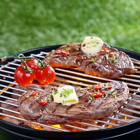 無駄のないステーキ バター、屋外の芝生の上の赤の熱い炭の上のバーベキューのグリル ハーブをトッピングのおいしい部分