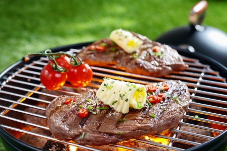 garden barbecue: Succulent portion of lean steak topped with butter and herbs grilling on a grid over hot coals in a barbecue