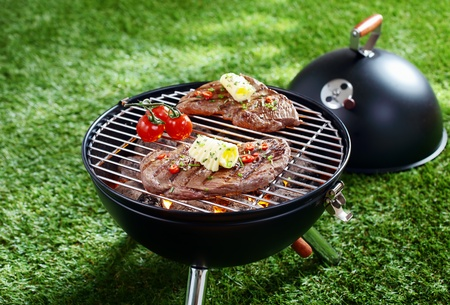 coals: High angle view of two succulent steaks cooking on a barbecue over the hot coals on a green lawn outdoors