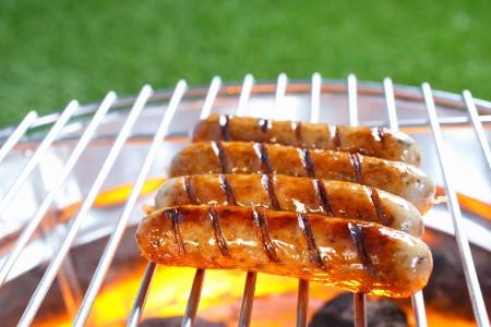 chorizos asados: Fila de carne y salchichas de cerdo en una barbacoa chisporrotea caliente sobre carbones encendidos mientras se cocinan en una barbacoa al aire libre saludable
