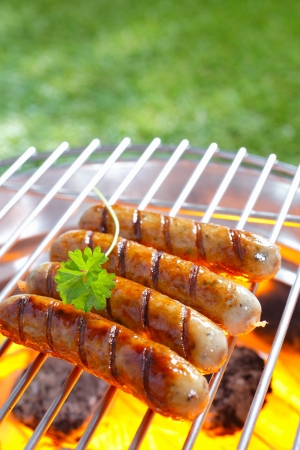 bbq background: Delicious grilled sausages resting on the iron grid of a portable barbecue over glowing coals as they cook to perfection