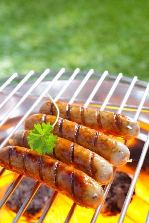 embutidos: Salchichas a la parrilla deliciosos descansando en la parrilla de hierro de una barbacoa portátil sobre carbones encendidos mientras se cocinan a la perfección Foto de archivo