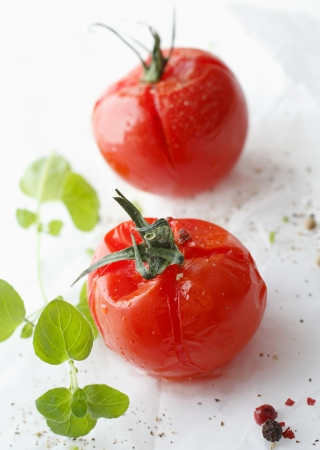 Succulent grilled cherry tomatoes with fresh thyme ready to be served as a vegetable with a meal Banco de Imagens