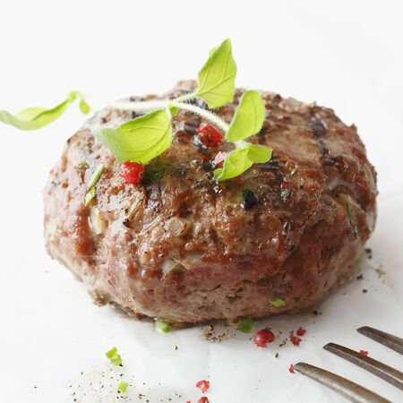 Closeup of a tasty seasoned meatball made from ground or minced beef garnished with herbs served on a white plate photo
