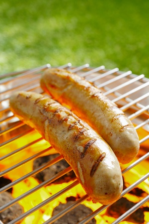 sizzling: Grilled Bratwurst on the grilling pan outdoors Stock Photo