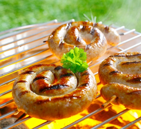Close up shot of spiral sausages on the grilling pan photo