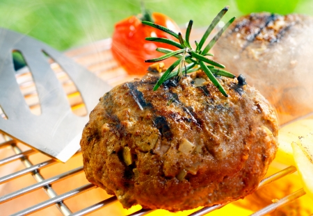 minced beef: Hamburger patty grilling on the barbecue isolated on