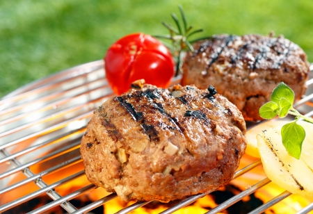garden party: Beef burgers cooking on grilling pan outdoors