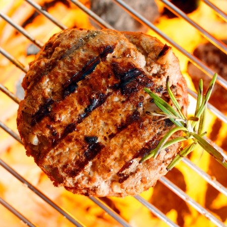 ground beef: Hamburger patty on the grilling pan with open flames Stock Photo