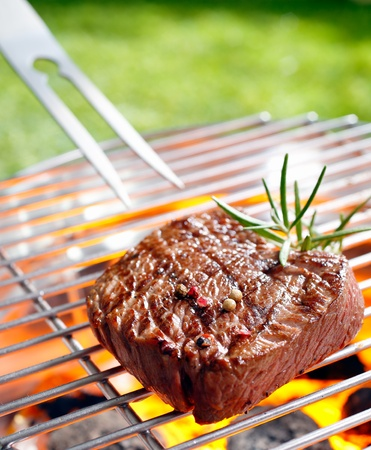 Grilled beef steak on the grilling pan outdoors Stock Photo