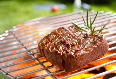 charcoal grill: A thick strip steak being grilled outdoors