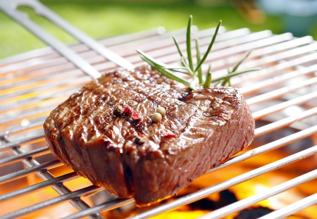 Grilled marinated steak on the grilling pan with open flames