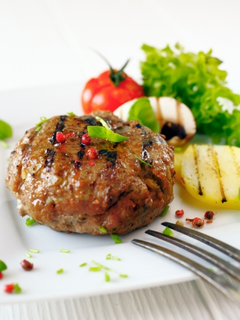 menue: Succulent cooked beef burger with potatoe and salad on a white plate. Stock Photo