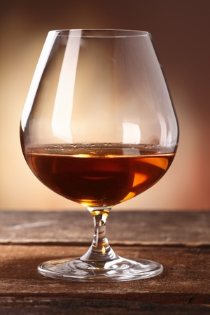 cognac: Glowing golden brown cognac served in a snifter as a luxury after dinner beverage