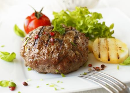 HAMBURGESA: Delicioso meatball sector de la carne a la parrilla servido en un plato blanco con tomate y lechuga con un tenedor en el primer plano