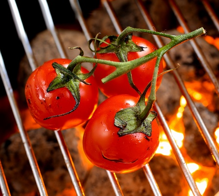 Bunch of ripe red cherry tomatoes on the vine roasting over a barbecue fire, high angle view of the grid and glowing charcoal photo