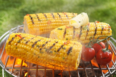 Healthy vegetarian barbecue with ripe golden corn on the cob and juicy red cherry tomatoes grilling over the fire outdoors on a green lawn Stock Photo