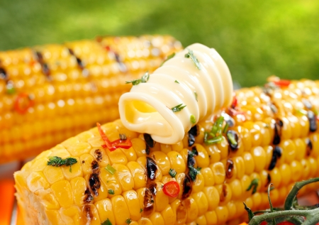 Delicious golden grilled corn on the cob served outdoors with a curl of fresh farm butter