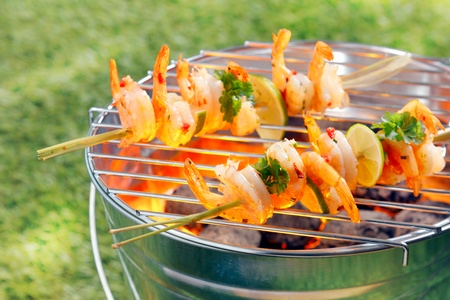 Seafood kebabs with gourmet shelled fresh prawns roasting over the fire on a portable barbecue outside on green grass