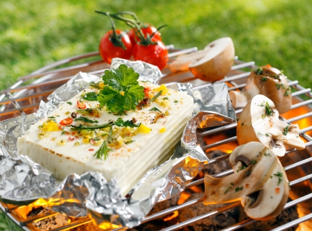 Large portion of seasoned halloumi or feta cheese grilling in tin foil over hot coals in a barbecue outdoors on green grass photo