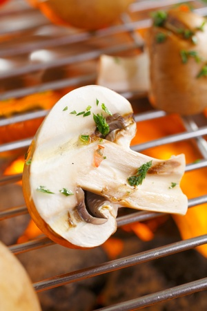 flavouring: Fresh halved mushrooms sprinkled with chopped herbs for flavouring grilling over a barbecue fire