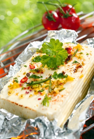 A delicious portion of feta cheese or halloumi topped with fresh herbs and spices grilling on an outdoor barbecue Stock Photo - 18995356