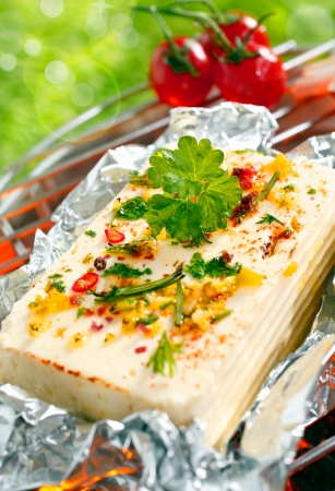 Halloumi cheese topped with fresh herbs and spices grilling in tin foil over the glowing coals of a barbecue outdoors in the sunshine Stock Photo - 18995306