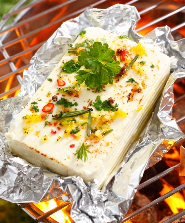 High angle view of a portion of feta or halloumi cheese topped with seasoning and spices grilling on a barbecue Stock Photo - 18995327