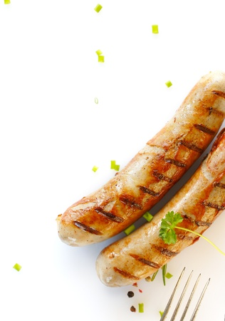 prongs: Two cooked sausages side by side against showing prongs of a fork against a white background. Stock Photo
