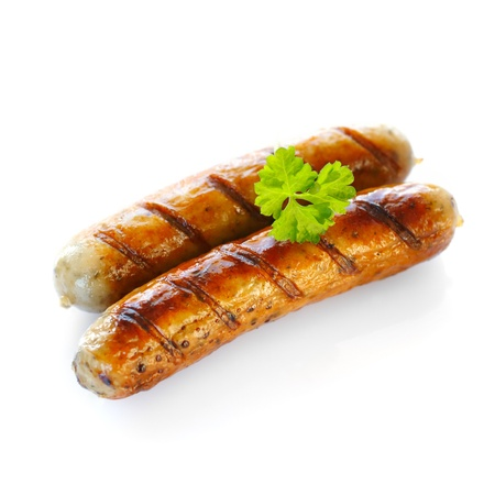 bratwurst: Close up of two cooked sausages, focus on the one at the front with a sprig of parsley on top against white background.
