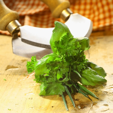 Bouquet garni of fresh herbs including basil, crinkly leaf parsley and chives lying on a wooden table in front of a chopping blade Stock Photo - 18995380