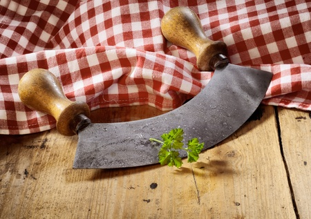 Modern herb cutter (wiegemes) with wooden handles with a sprig of parsley against a red gingham cloth. Stock Photo - 18995087