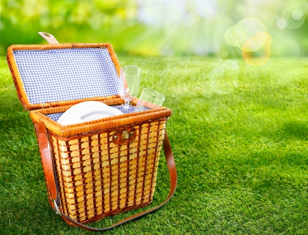 hamper: Pretty wicker picnic basket with a fresh blue and white lining standing open on a sunny green summer lawn to display plates and glasses