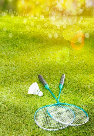Badminton rackets and shuttlecock lying on a lush green lawn in warm golden summer sunlight with flare and bokeh photo